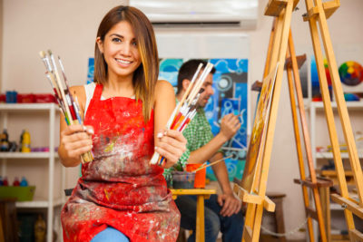 45584179 - portrait of a gorgeous young brunette wearing an apron and holding a bunch of paintbrushes in an art class